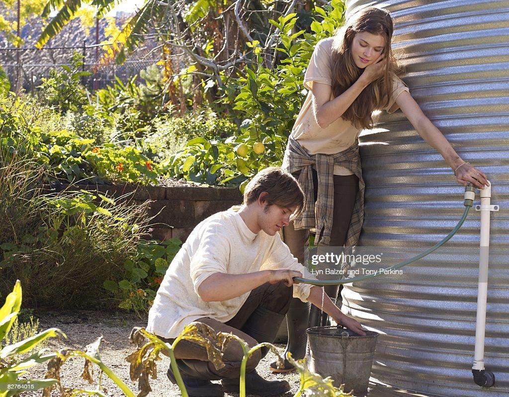 Teens filling up water bucket at water tank : Stock Photo