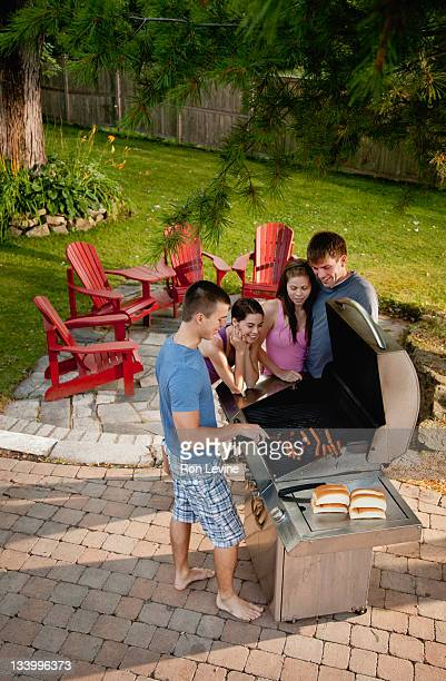 Teens having a BBQ in suburban backyard
