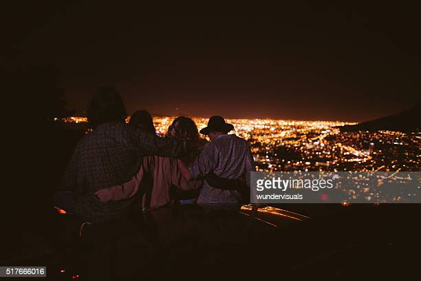Teens hugging on a convertible looking at night city lights