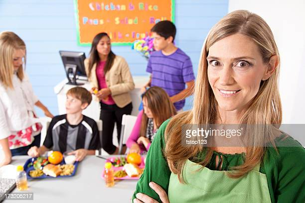 Teens in school cafeteria eating lunch.  Menu on wall
