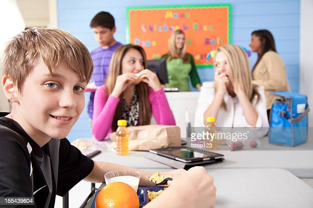 Teens in school cafeteria sharing lunch, friendships and conversation