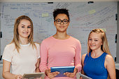 Three female teenagers are posing for the camera at school. They are standing in front of the whiteboard and are smiling at the camera, holding digital tablets and workbooks.