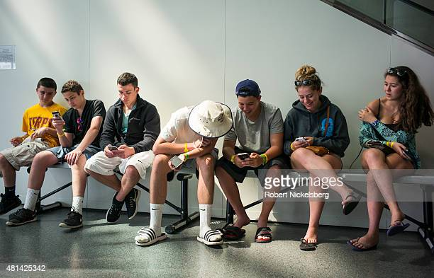 Teens look at their iPhones July 3 2015 at the Rock and Roll Hall of Fame in Cleveland Ohio