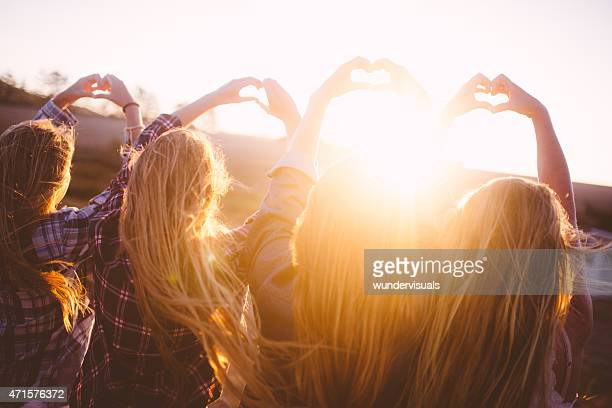 Teens making heart shapes with their hands at sunset