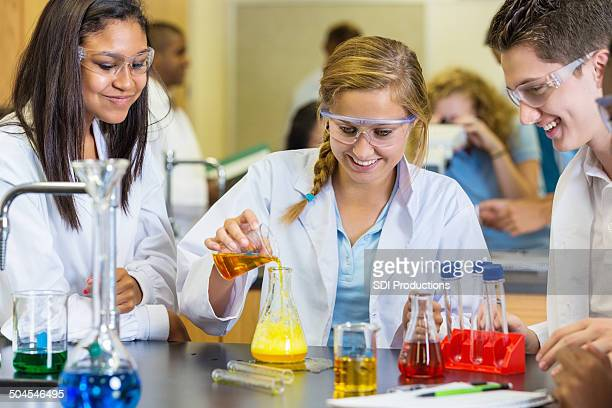 Teens mixing chemicals during science experiment in classroom