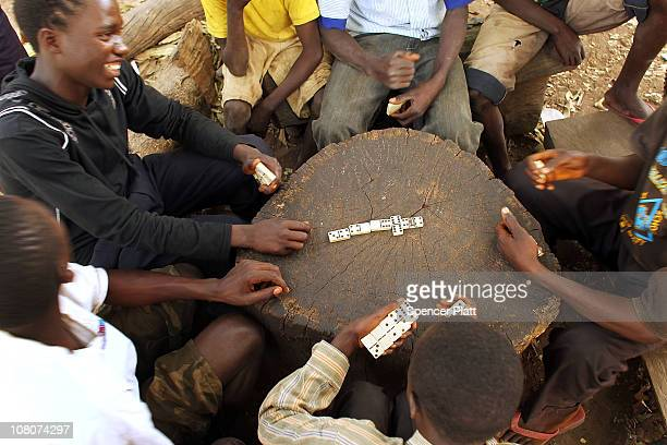 Teens play a game of dominoes along a road in the countryside on the first day after the conclusion of the referendum vote January 16 2011 in the...