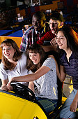 Teens Playing Auto Racing Video Game in an Arcade