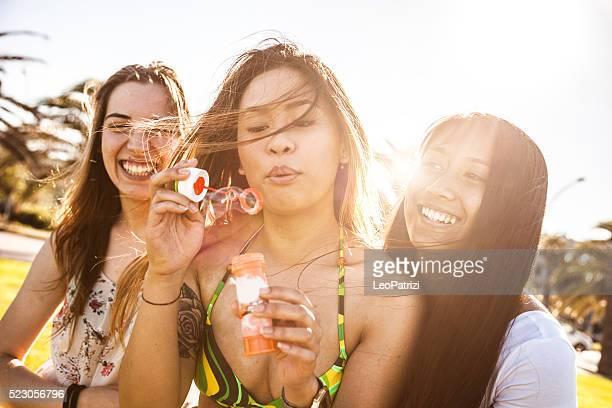 Adolescentes Jogando com bolhas no parque