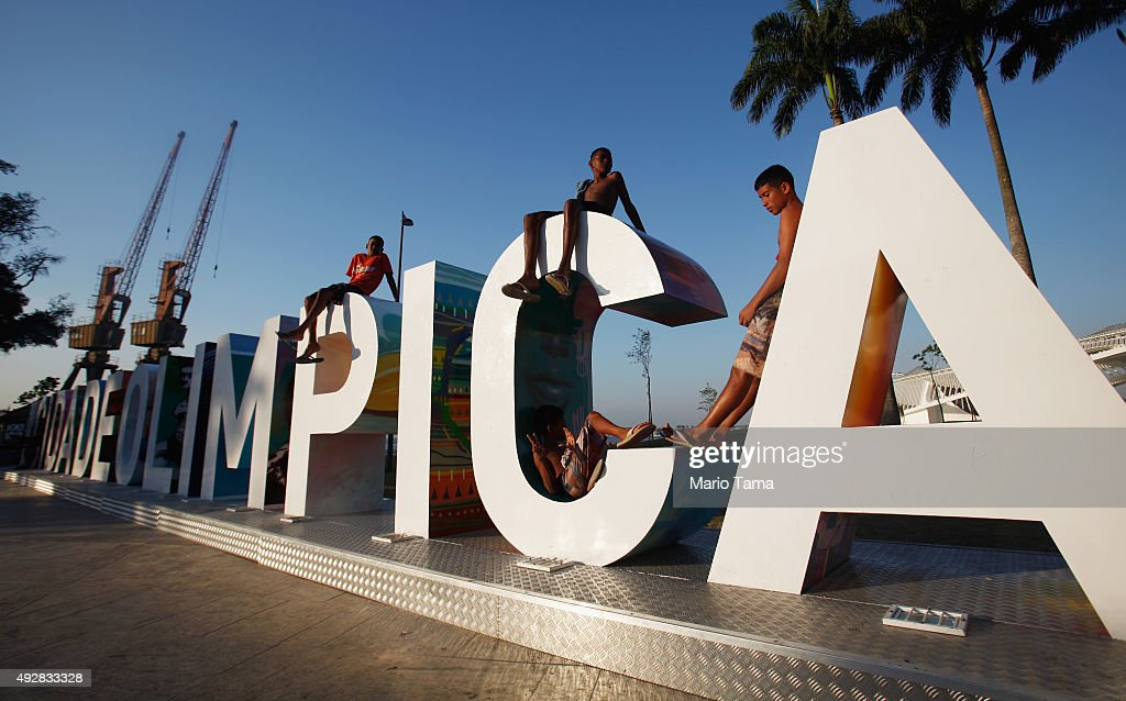 Teens sit on a new sign reading 'Cidade Olimpica' in the historic port district on October 15 2015 in Rio de Janeiro Brazil Ahead of the Rio 2016...