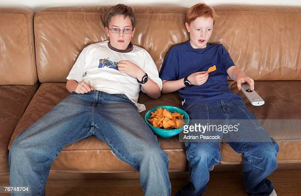 Teens sitting on couch eating a snack and watching TV