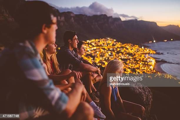 Teens sitting on mountain at sunset with city lights beyond