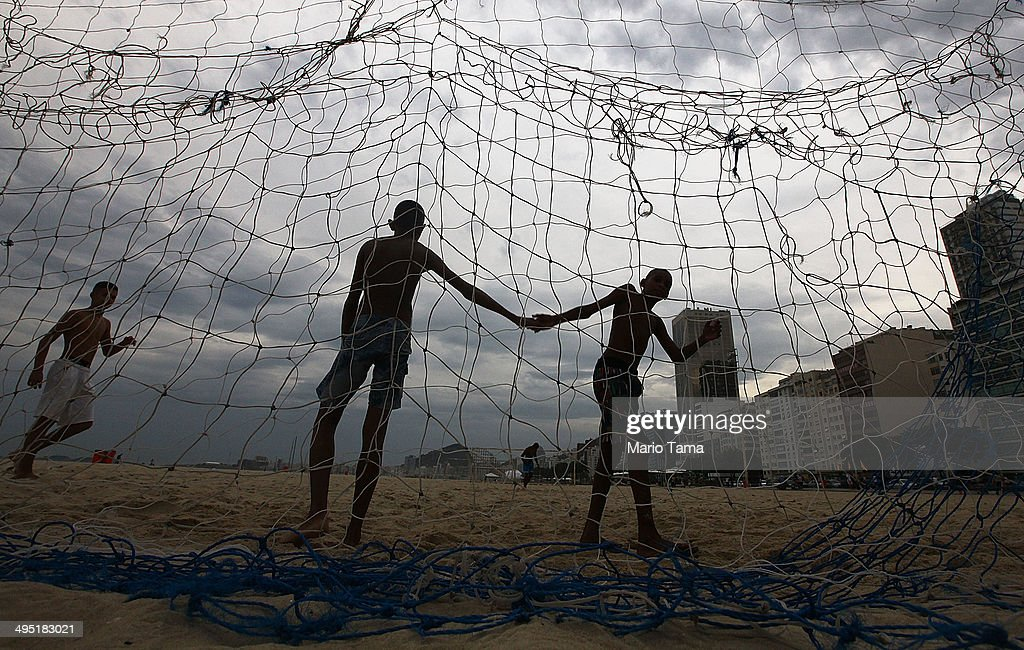 Teens slap hands while playing soccer on Copacabana Beach on June 1, 2014 in Rio de Janeiro, Brazil. Brazil has won five World Cups, more than any other nation. The 2014 FIFA World Cup kicks off June 12 in Brazil.