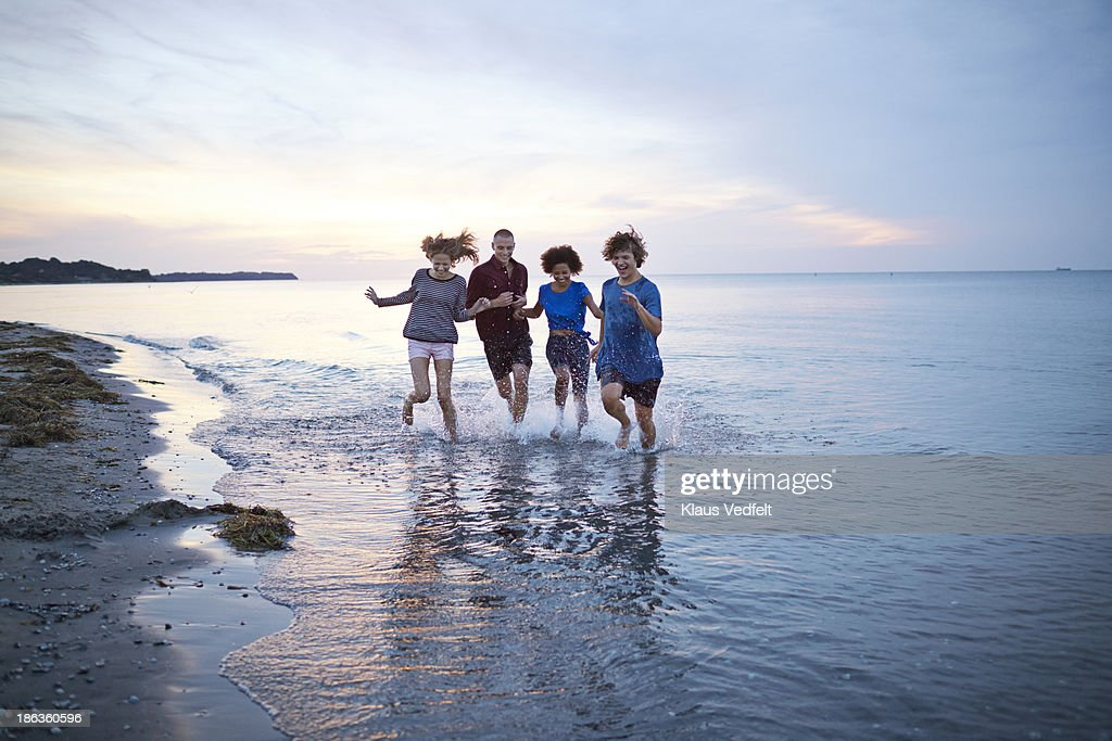 Teens sprinting in the ocean in the sunset
