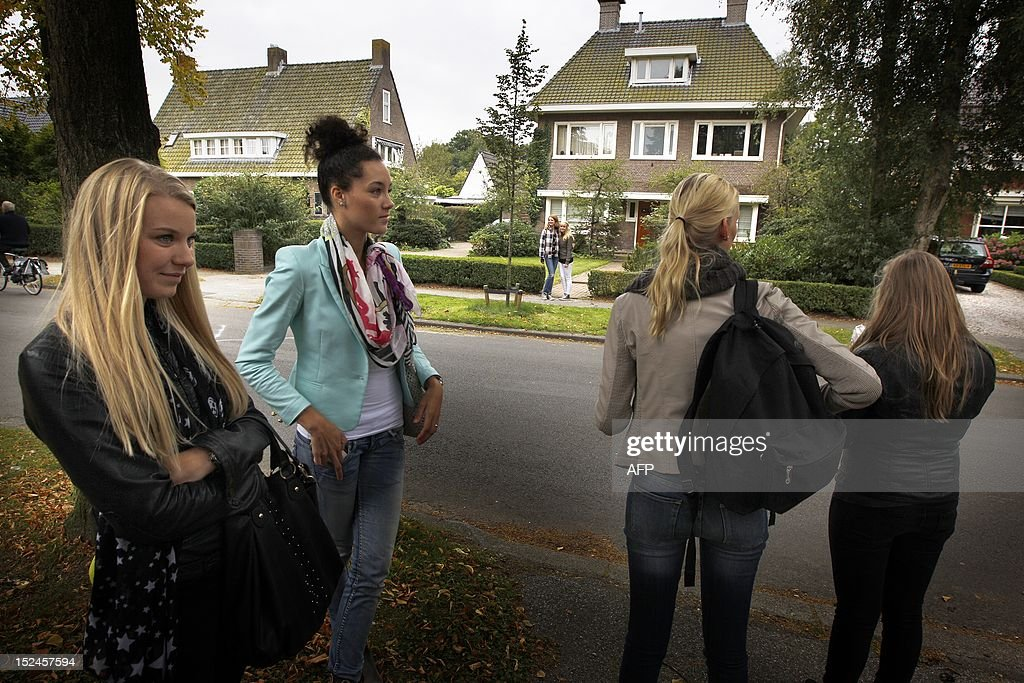 Teens stand in front of the house of a teenager who send a public Facebook party invite in Haren, on September 21, 2012. Police officers in Haren near the northern city of Groningen were on high alert after the schoolgirl posted a message inviting friends to her 16th birthday party on September 21, but forgot to mark it as a private event. 'She posted the invitation on Facebook and sent it to friends, who then sent it to other friends and soon it spread like wildfire across the Internet,' Groningen police spokeswoman Melanie Zwama told AFP.