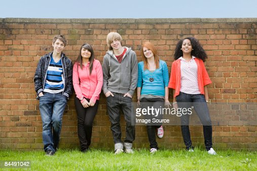 Teens standing by wall : Stock Photo