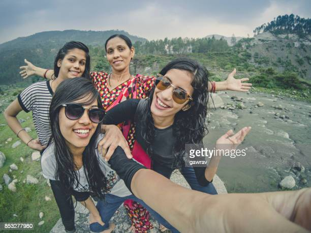 Teens taking selfie with family in hills.