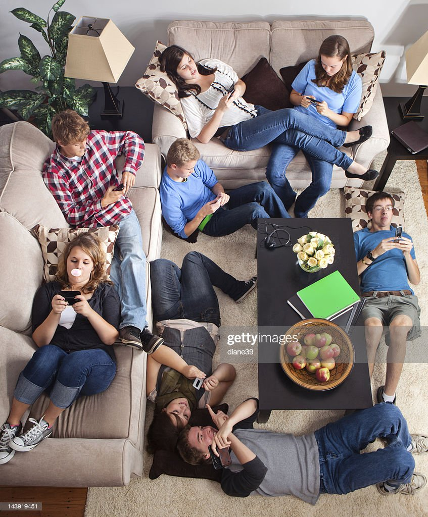 Teens texting in a living room : Stock Photo