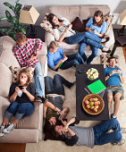 A group of teenagers in a home setting texting on cellphones.