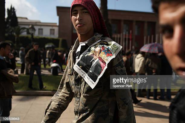 Teens with a crumpled picture of King Mohammed VI jointhousands of Moroccans demonstrate against the regime led by King Mohammed VI on February 20...