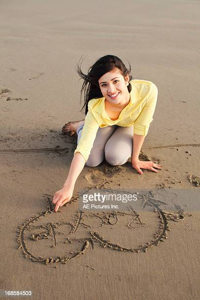 Teens writes recycle in sand