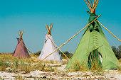 Three teepees on the sea shore