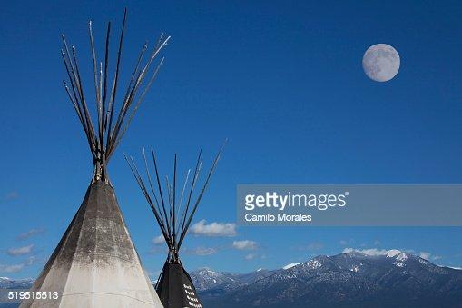 Teepees under full moon in blue sky