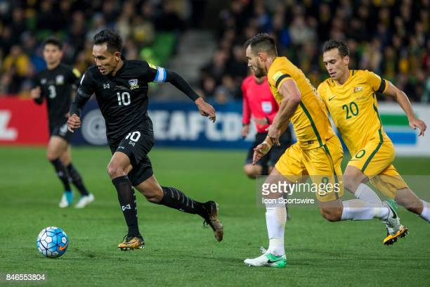 Teerasil Dangda of the Thailand National Football Team runs with the ball in front of Bailey Wright of the Australian National Football Team and...