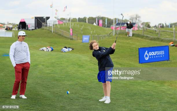 Tegan Hancox is watched by Thorbjorn Olesen of Denmark during a Golf Foundation GolfSixes Academy event at prior to the start of GolfSixes at The...