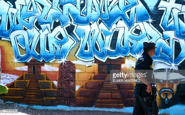 A policeman passes by a graffiti of the Mara Salvatrucha 'MS13' at the entrance of the unit where members of the gang are kept imprisioned in the...