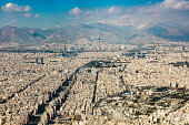 Aerial view of urban sprawl. Tehran, Iran metropolitan area (population 12.2 million in 2012) with the snowcapped Alborz (Elburz) mountains behind. Canon EOS 5Ds, 70 mm.
