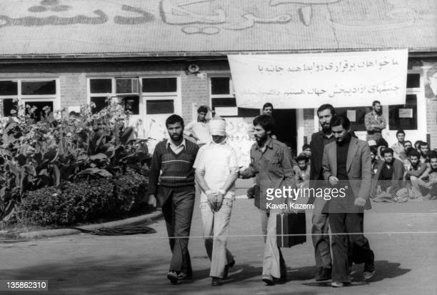A blindfolded American hostage with his hands tied up is brought out on to the compound of the embassy by students who stormed the embassy and took...