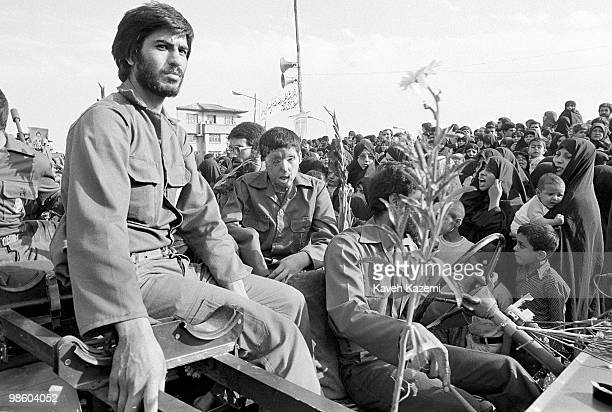 A veteran Revolutionary Guard in military fatigue and and his face severly deformed in IranIraq war along with his fellow Pasdars are greeted by...