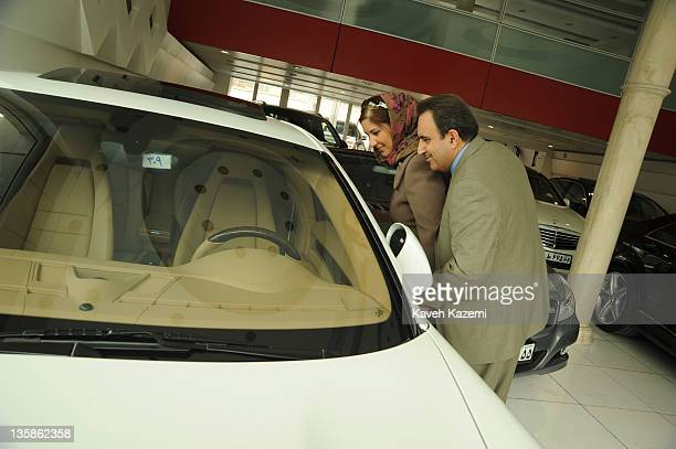 A welltodo couple look at a brand new Porsche Cayenne in a car showroom filled with 2011 model cars in Tehran 11th March 2011