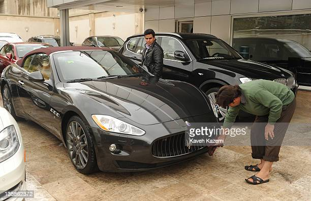An Afghan man cleans a brand new Maserati with street value of 300000 USD in a car showroom in Tehran 9th November 2011