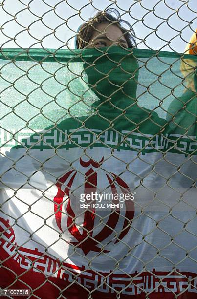 An Iranian woman holding a national flag watches a training session of Iran's national football team from behind a fence as females were not allowed...