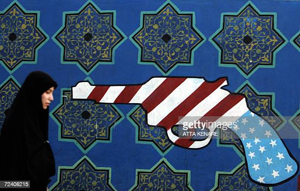 An Iranian woman walks past a mural painting of a revolver on the walls of the former US embassy in Tehran during a protest marking the 27th...