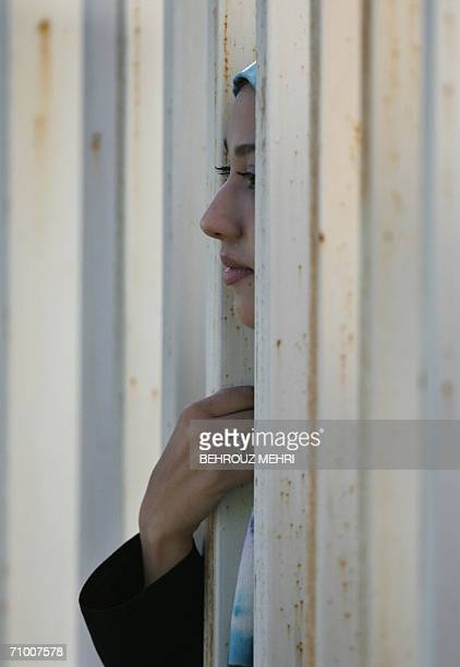 An Iranian woman watches a training session of Iran's national football team from behind a fence as females were not allowed to enter the stadium at...