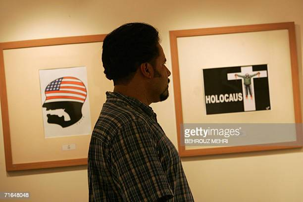An visitor looks at cartoons displayed at the international Holocaust cartoon contest in Tehran 14 August 2006 A leading Jewish organisation sounded...