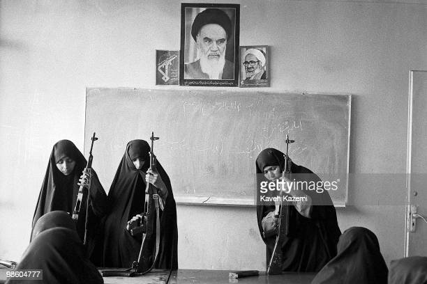 Basiji women wearing black chadors familiarise with AK47 an automatic assault rifle in a school classroom in west Tehran as part of mass mobilisation...