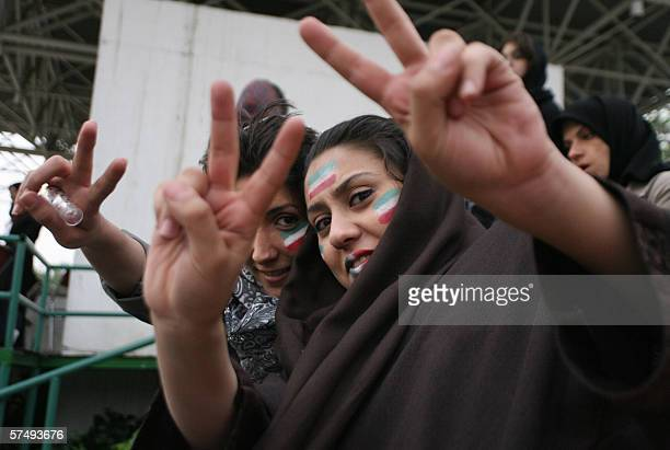 Iranian women who painted the Islamic republic's flag on their faces and lips flash the Vsign for victory during a football match between Iran's...
