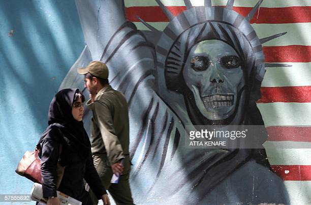 Iraniana walk past an antiUS mural painting depicting the Statue of Liberty on the wall of the former US embassy in Tehran 08 May 2006 Iranian...