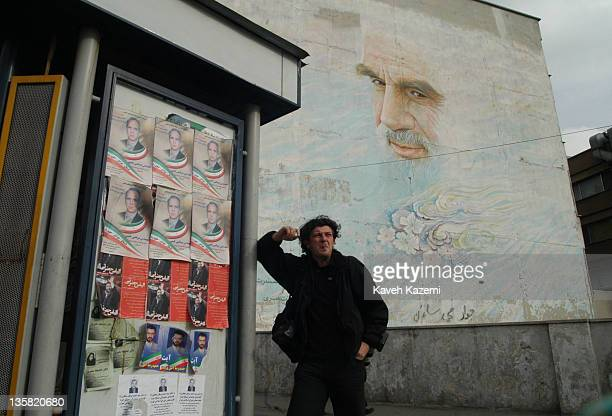 Reuters agency photographer Damir Sagolj a Bosnian war veteran stands smoking a cigarette in front of a huge mural of Ayatollah Khomeini in Vanak...