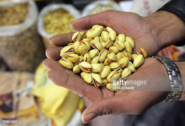 TO GO WITH AFP STORY BY ARESU EQBALI A pistachio wholesaler shows his goods at his shop in Tehran 18 November 2006 Almost 10 years after an EU ban...
