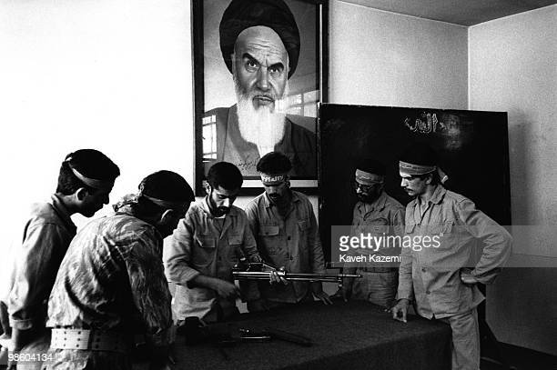 Under watchful eyes of Ayatollah Khomeini a group of Basiji men in a Tehran factory learn to use fire arms as part of mass mobilisation in the final...