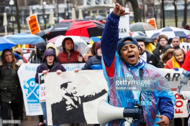 Teiarra Davis raises her fist as she marches in a protest to support workers fighting for $15/hour and union rights at the Boston Common in Boston on...