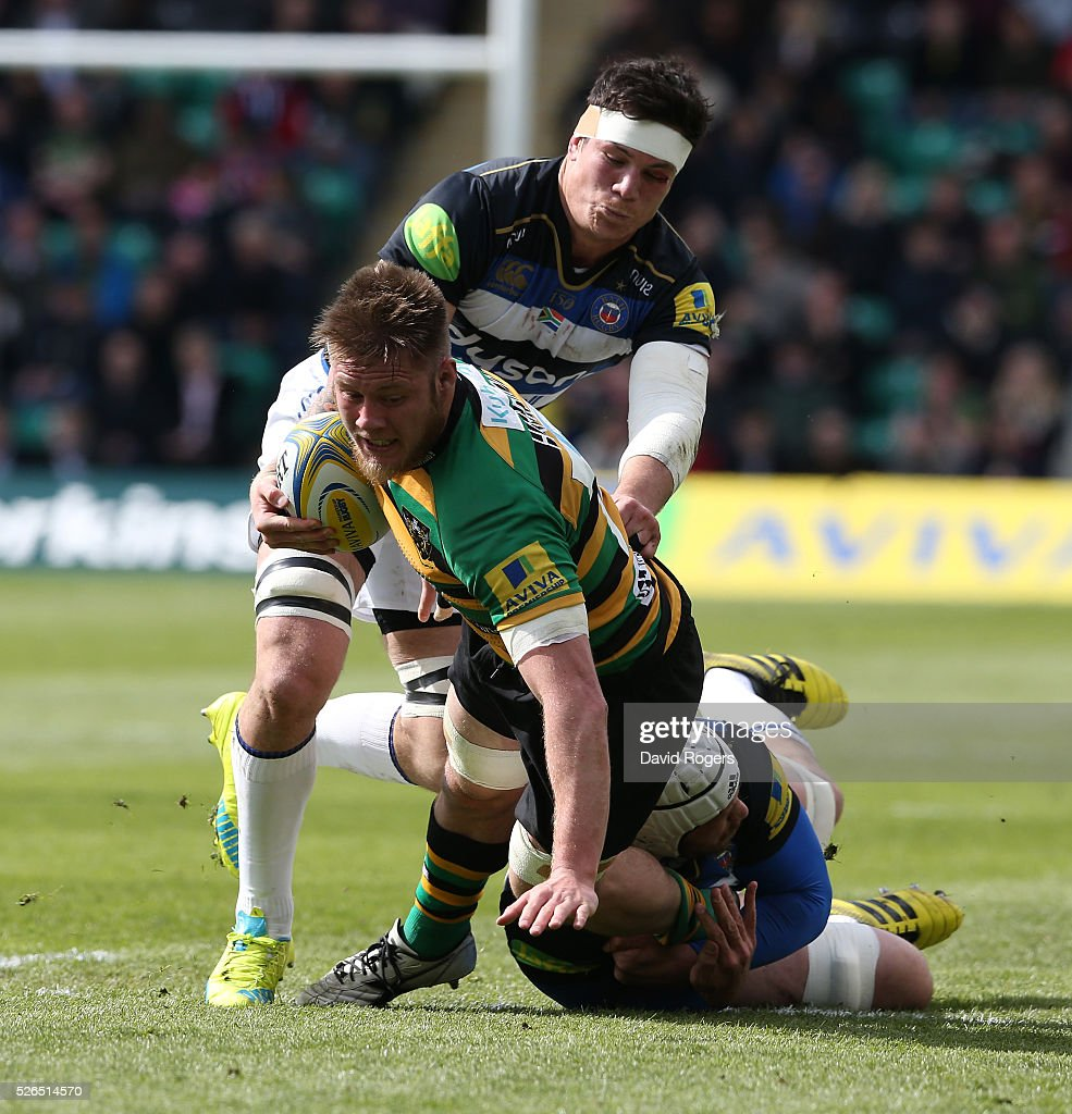 Teimana Harrison of Northampton is tackled by Francois Louw (L) and Dave Attwood during the Aviva Premiership match between Northampton Saints and Bath at Franklin's Gardens on April 30, 2016 in Northampton, England.