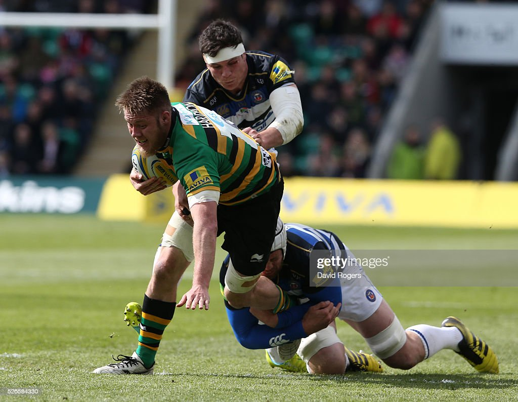 Teimana Harrison of Northampton is tackled by <a gi-track='captionPersonalityLinkClicked' href=/galleries/search?phrase=Francois+Louw&family=editorial&specificpeople=4389467 ng-click='$event.stopPropagation()'>Francois Louw</a> (L) and <a gi-track='captionPersonalityLinkClicked' href=/galleries/search?phrase=Dave+Attwood&family=editorial&specificpeople=4134653 ng-click='$event.stopPropagation()'>Dave Attwood</a> during the Aviva Premiership match between Northampton Saints and Bath at Franklin's Gardens on April 30, 2016 in Northampton, England.