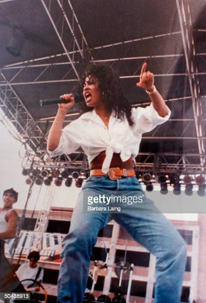 Tejano singer future murder victim Selena singing into mike on outdoor stage