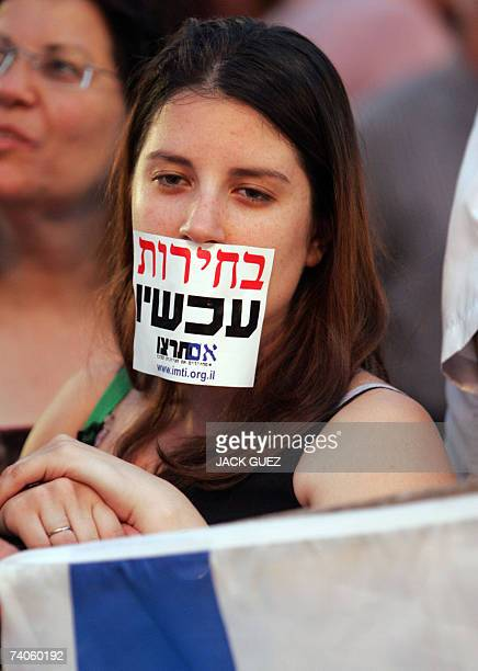 An Israel woman has her mouth sealed with a sticker that reads'Elections Now' as she and thousands of others gather in Tel Aviv's Rabin Square 03 May...