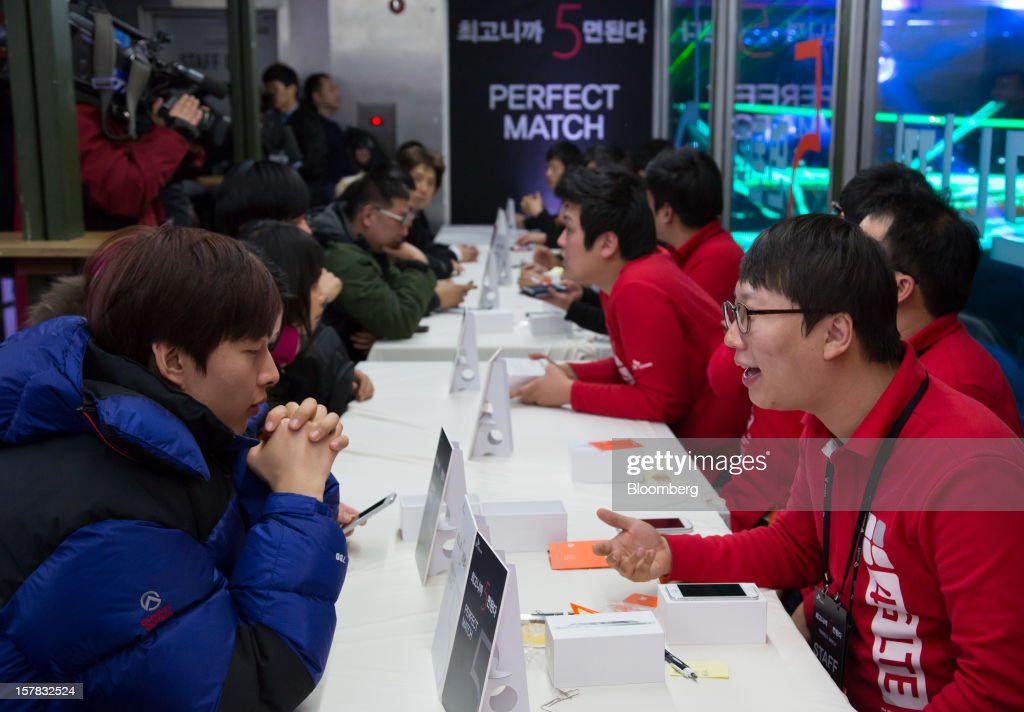 SK Telecom Co. employees, right, assist customers with their purchases of the Apple Inc. iPhone 5 during a launch event in Seoul, South Korea, on Friday, Dec. 7, 2012. The iPhone 5 went on sale in South Korea today. Photographer: SeongJoon Cho/Bloomberg via Getty Images